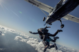 Le moment du largage lors d'un saut en parachute en tandem. Vue sur le ventre de l'avion et le dessus des nuages.